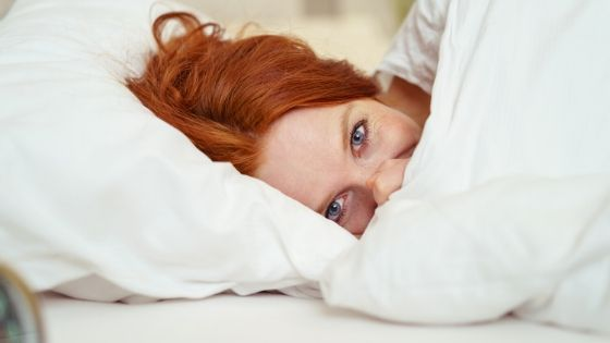 a woman looking comfy in her weighted blanket