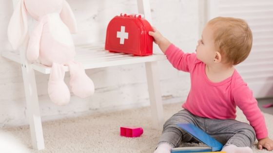 a baby playing with a pretend medicine box