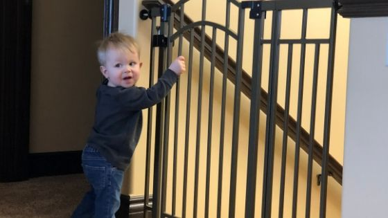a toddler by a baby gate