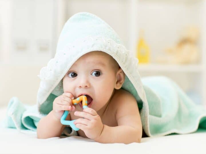 a young baby chewing on a teething toy