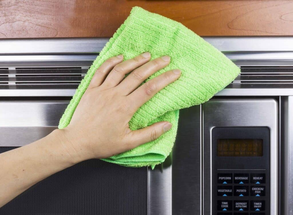 cleaning a microwave with a microfiber towel