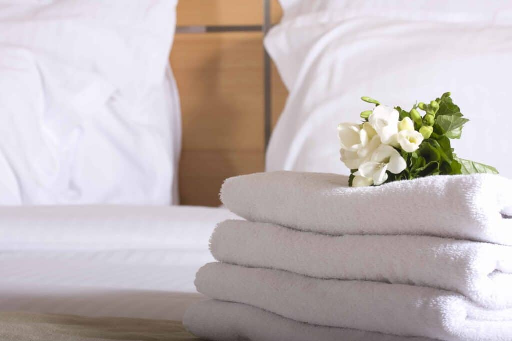 a clean bedroom with fresh towels and sheets