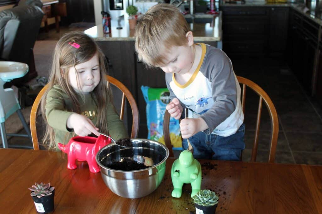 young kids gardening with dinosaur planters