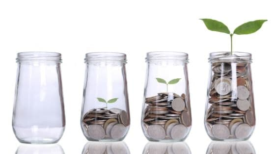 glass jars with money that is growing