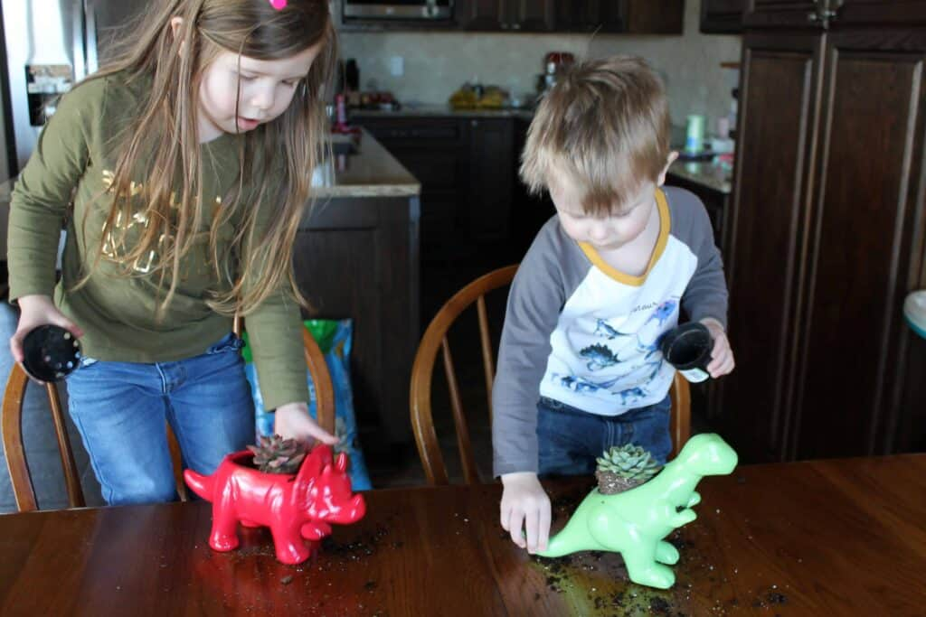two kids putting succulents into dinosaur planters