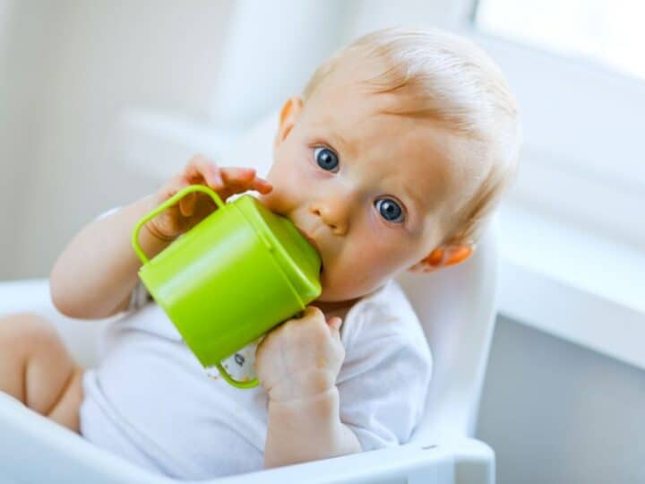 a 1 year old holding a sippy cup