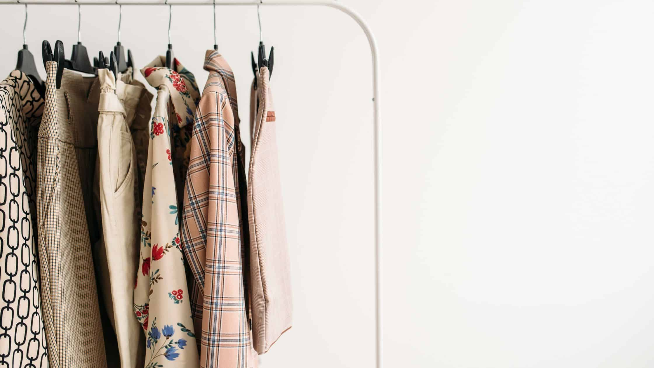 clothes from a capsule wardrobe hanging on a garment rack
