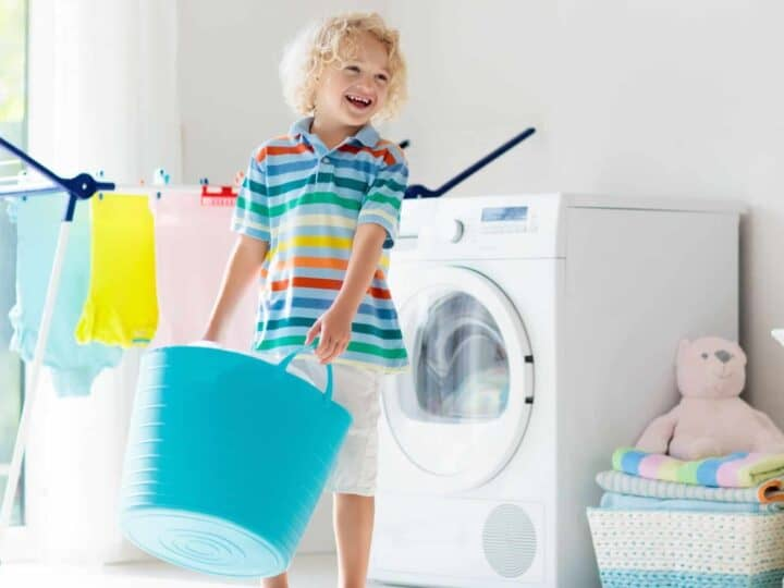 a boy holding a laundry hamper as he does his chores in the laundry room