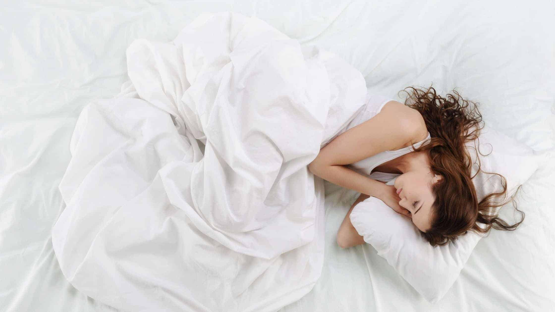 a woman sleeping comfortably in her sheets