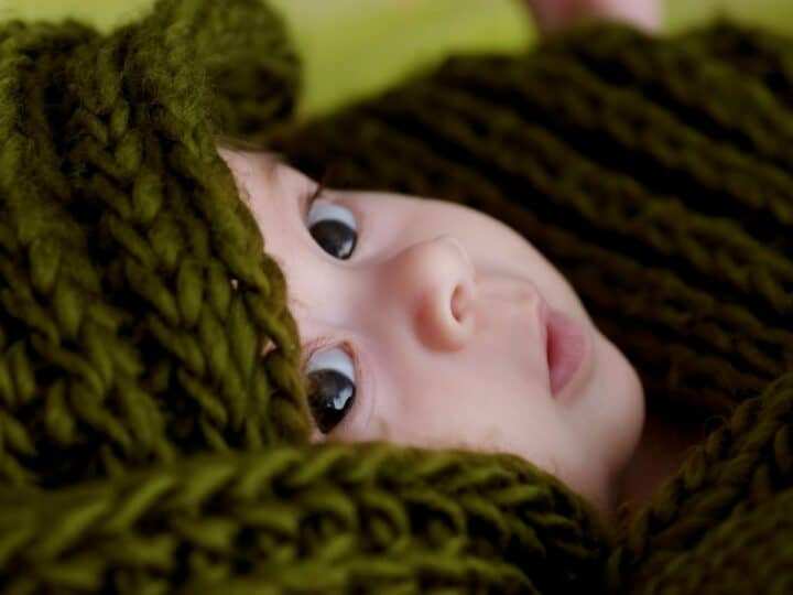 a baby wrapped in a dark green crochet blanket