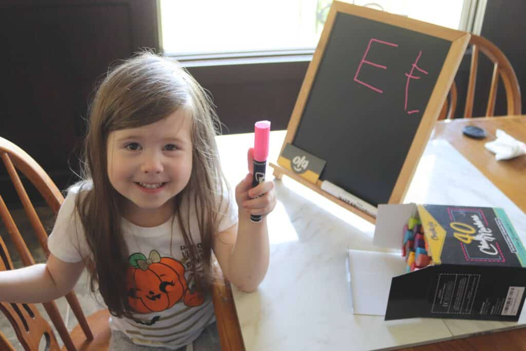 a girl holding a chalk marker next to a little chalkboard