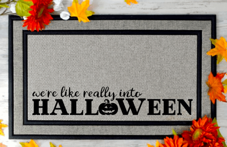 a doormat that says we're like really into halloween