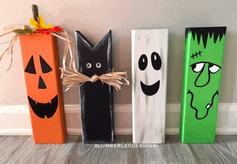 wood painted and cut to look like a jack-o-lantern, a black cat, a ghost, and frankenstein