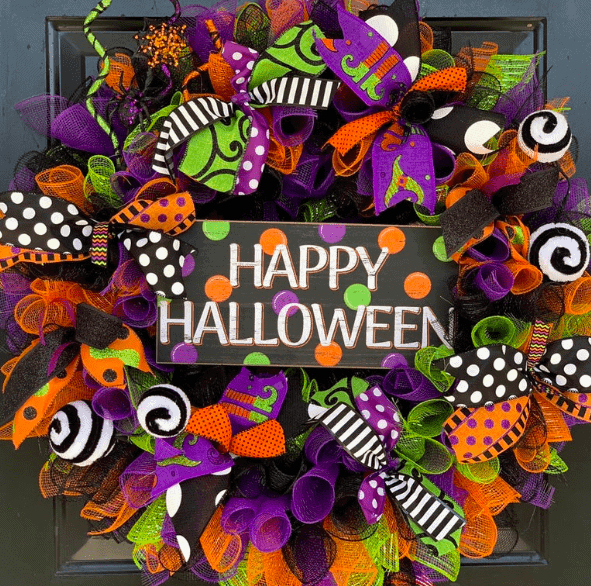 a colorful wreath with a sign that says happy halloween