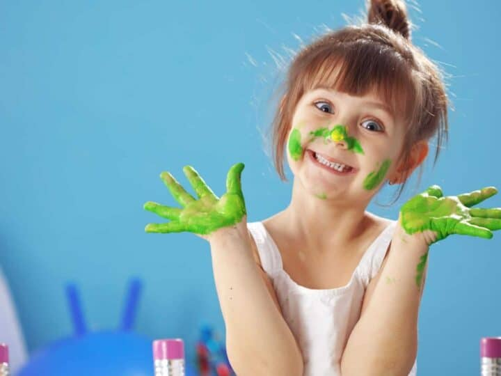a happy little girl with green paint on her hands and face