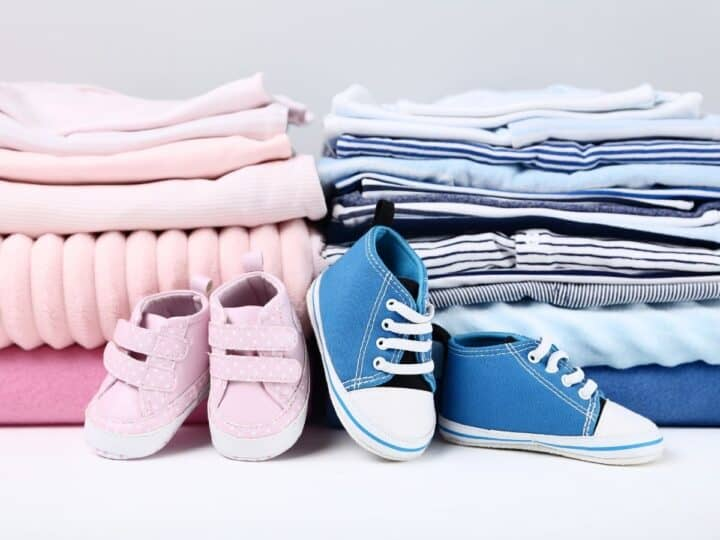 a stack of baby boy clothes and a stack of baby girl clothes
