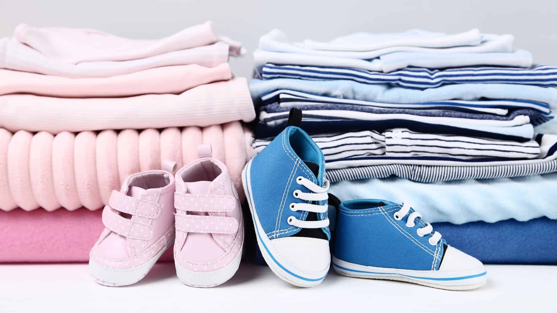 neatly stacked baby clothes in two piles of pink and blue with baby shoes in front too