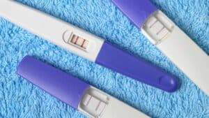 three positive pregnancy tests on a blue rug