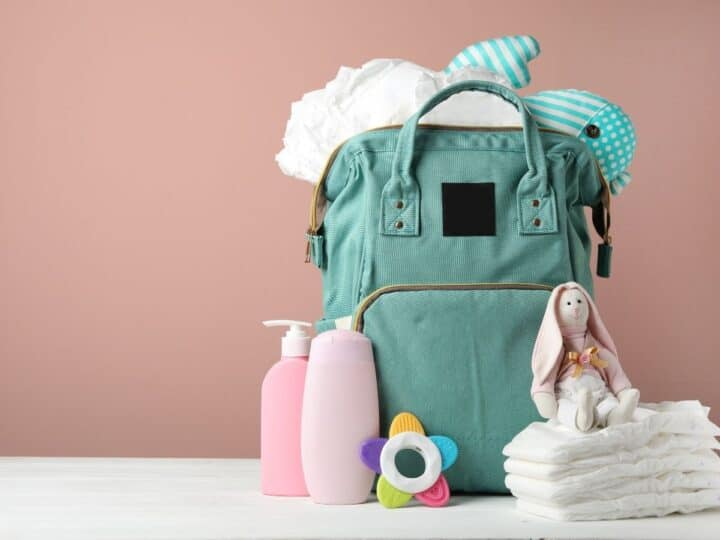 a mint green diaper bag with diapers and lotion beside it