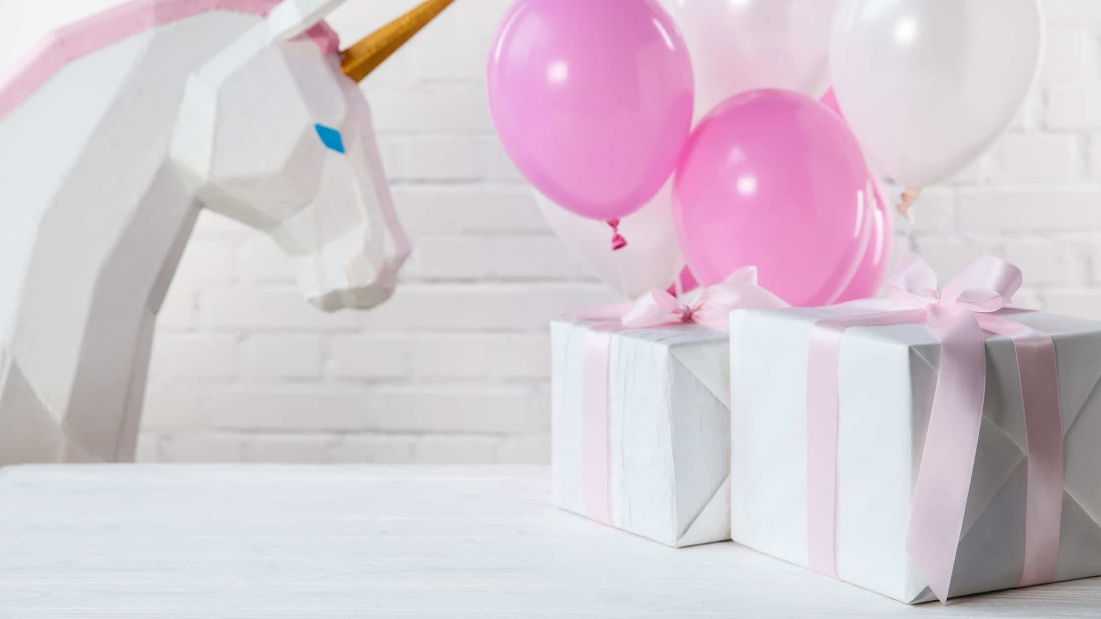 gifts wrapped with pink ribbon at a party with balloons and a unicorn