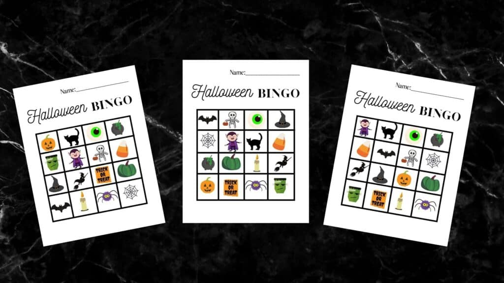 three halloween bingo card worksheets on a black marble counter top
