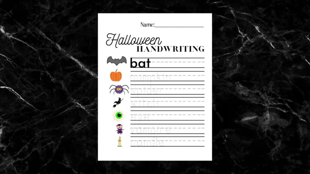 Halloween handwriting worksheet on a black marble counter top