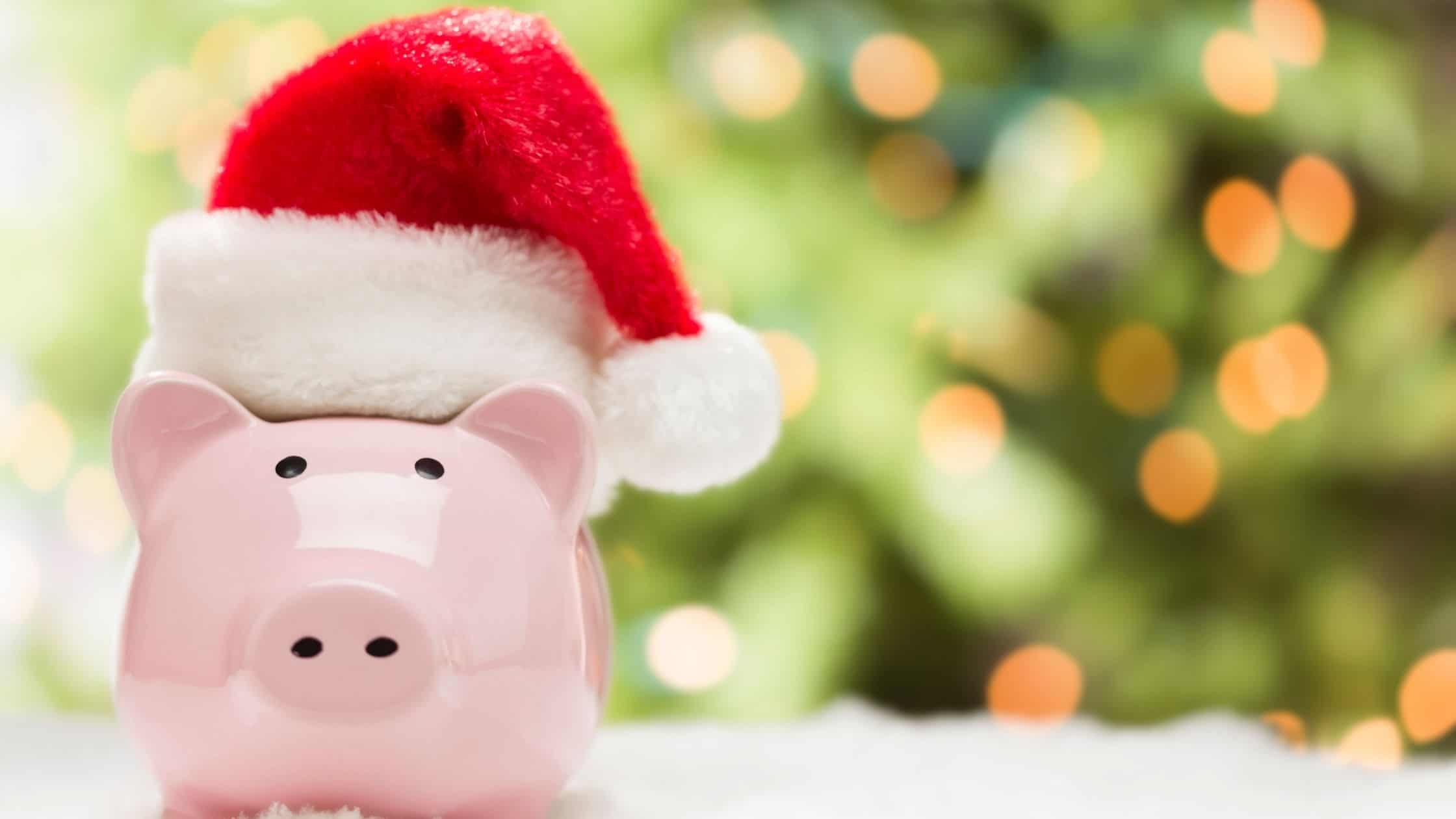 a pink piggy bank wearing a santa hat with a christmas tree in the background