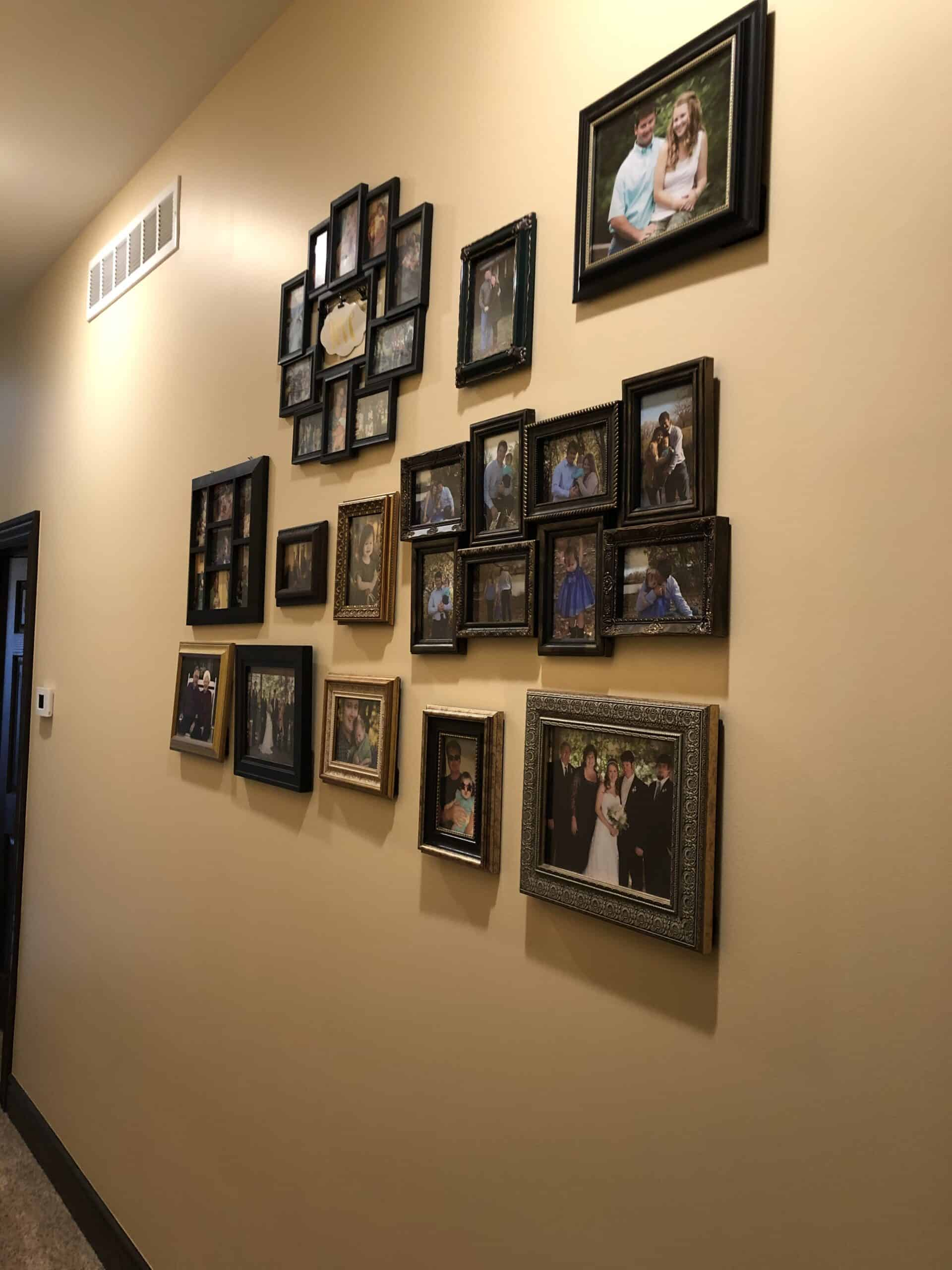 a hallway with picture frames hung up on the wall