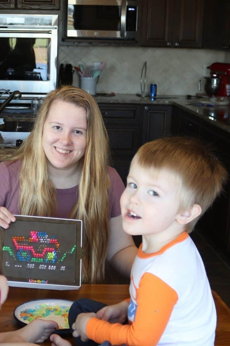 mom and kids playing with a retro lite brite toy