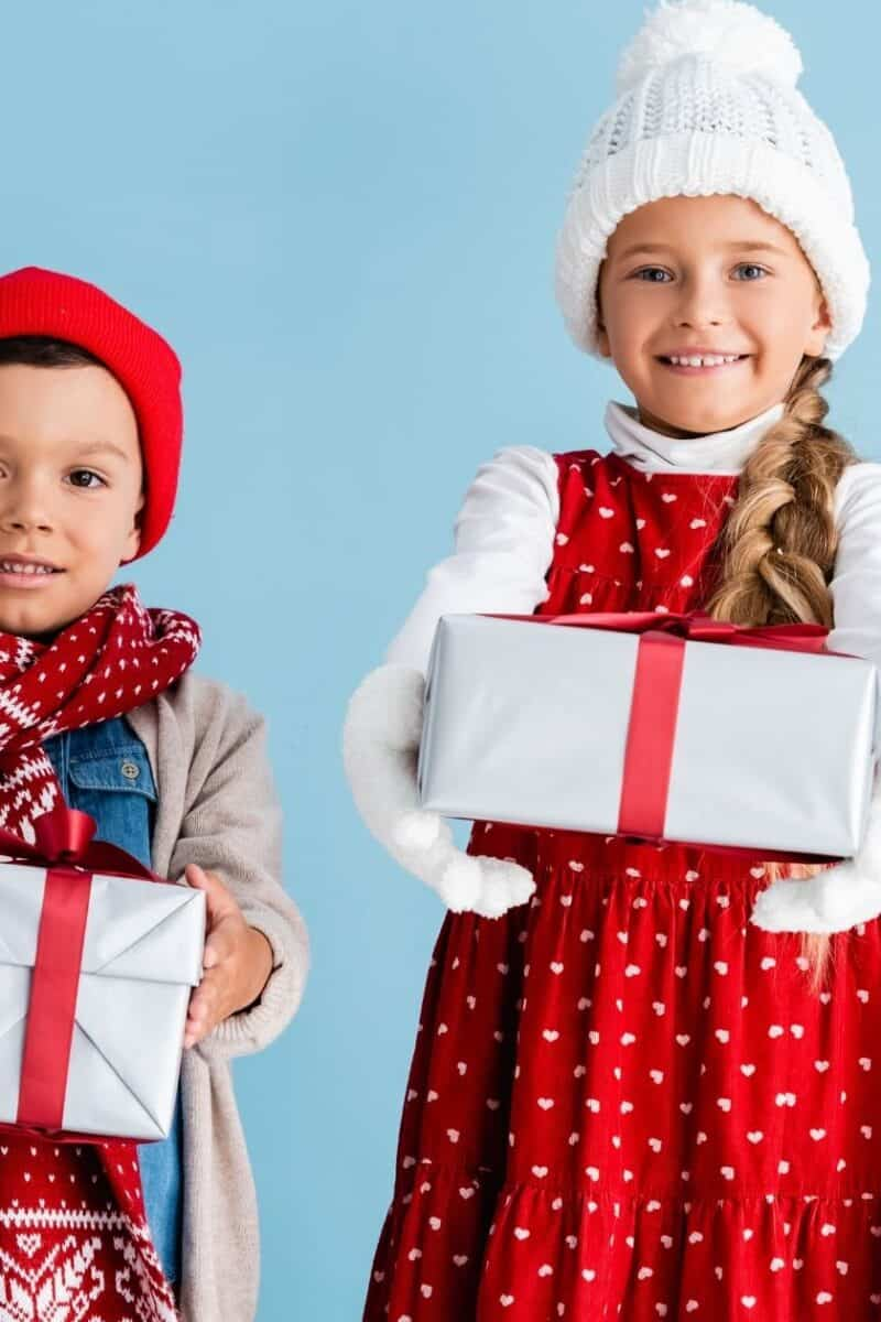 two kids holding presents by a christmas tree