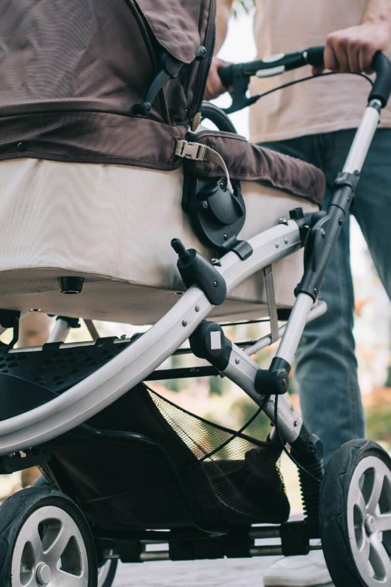 a mom and dad pushing a baby stroller in the park