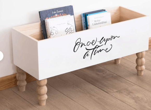 a white painted book shelf with wording that says once upon a time in script font