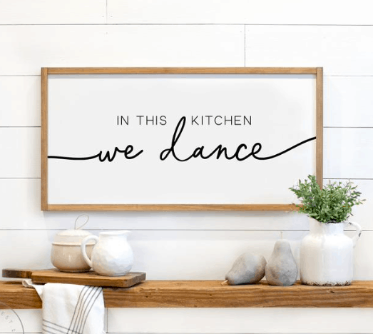"""a sign hanging up that says """" in this kitchen we dance"""""""