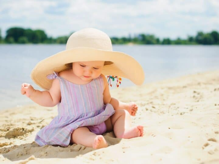 a little baby girl at the beach wearing a large sun hat