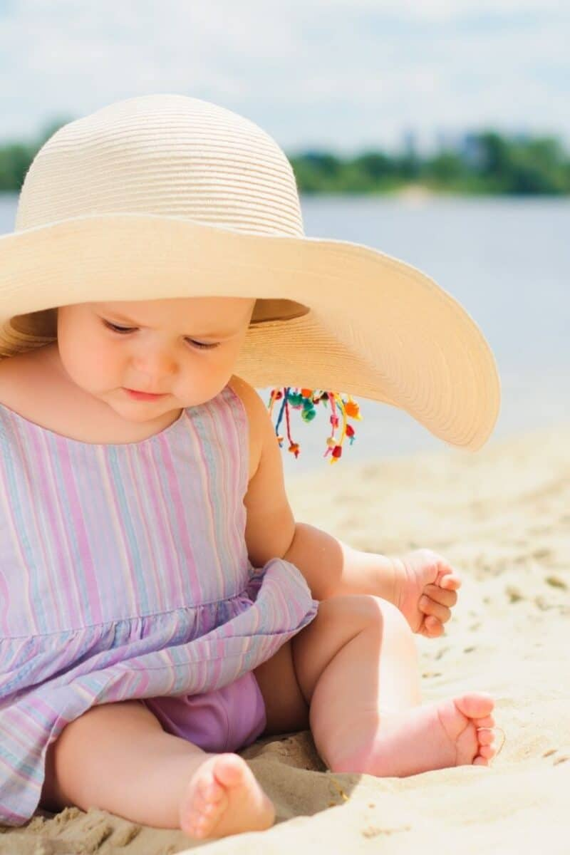 a baby wearing a sun hat at the beach