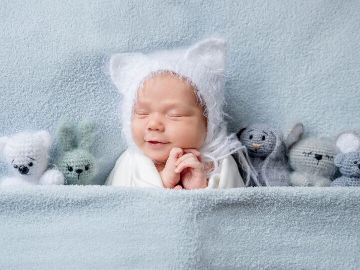 a baby snuggled up by some stuffed animals