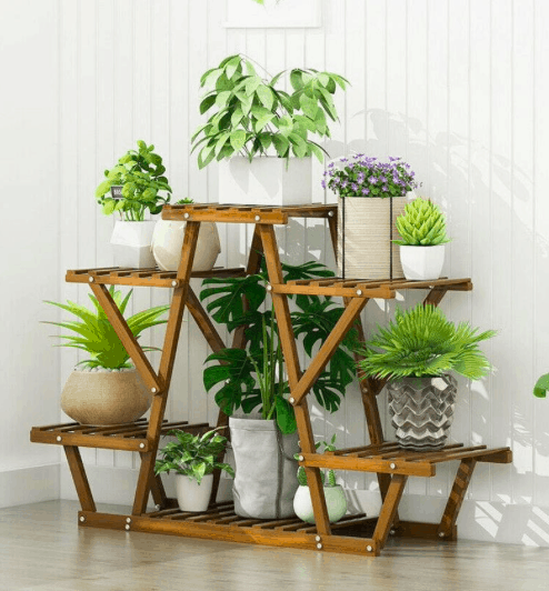 a wooden plant stand that allows for plants to drain