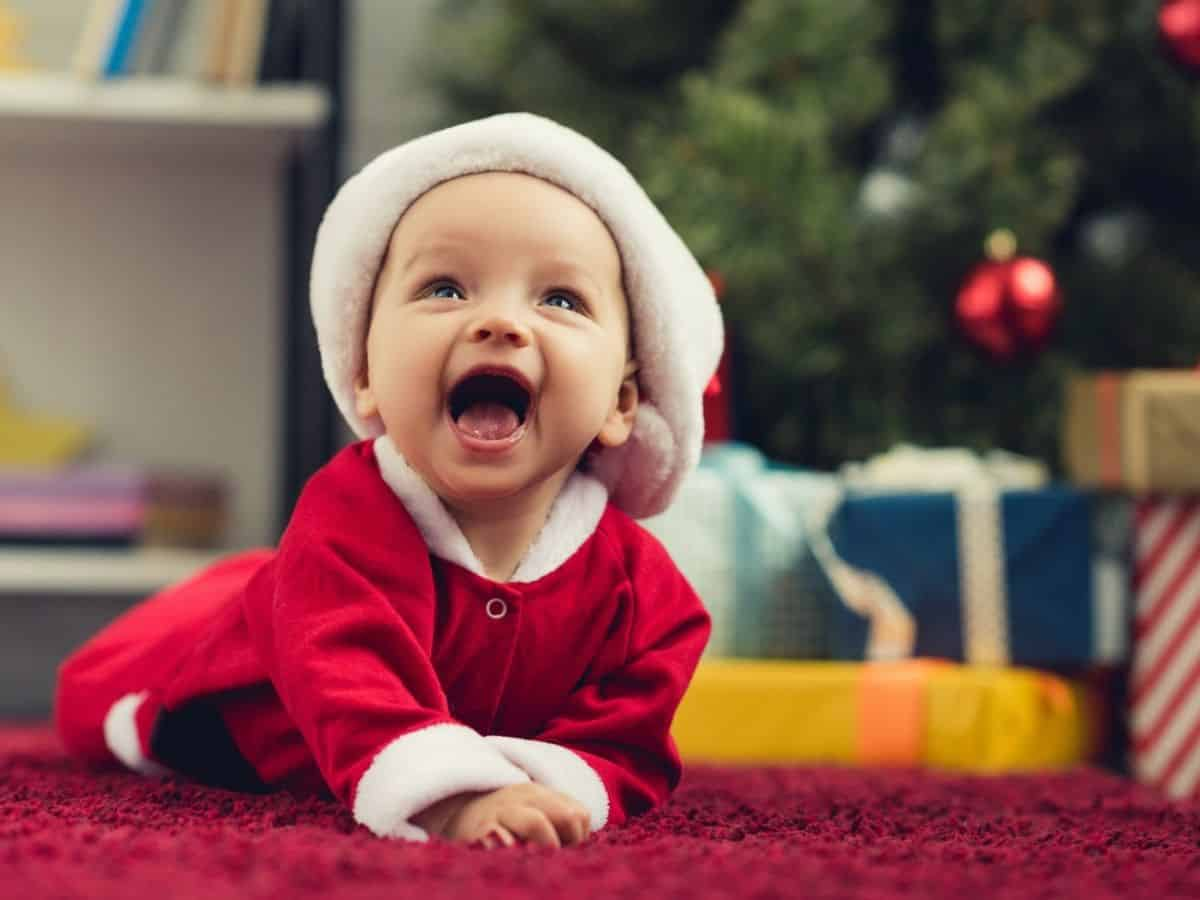 a smiling baby in a santa costume and a christmas tree in the background