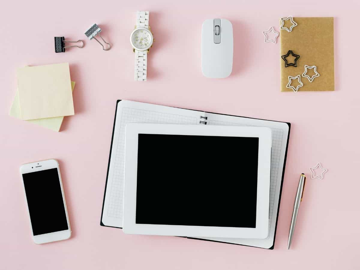 a flatly showing a computer tablet and phone along with a watch a computer mouse and notepads