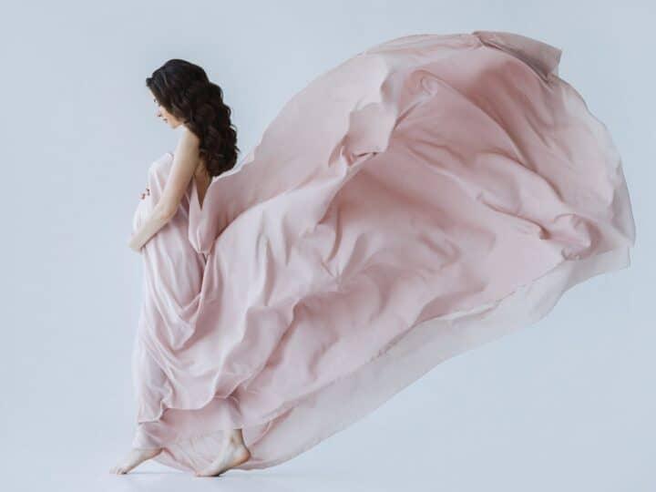 a pregnant woman wearing a beautiful dress