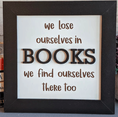 a framed artwork that says we lose ourselves in books we find ourselves there too
