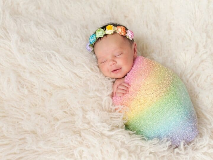 a baby with a rainbow blanket